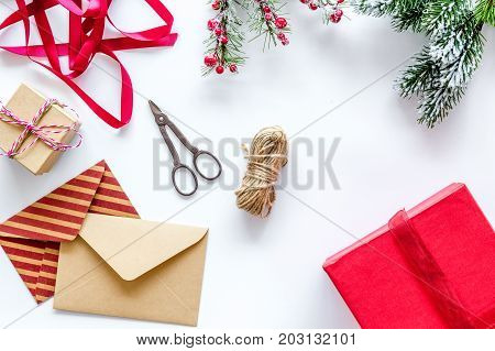 new year party preparation with gifts wrapping in boxes and envelopes on white desk background top veiw