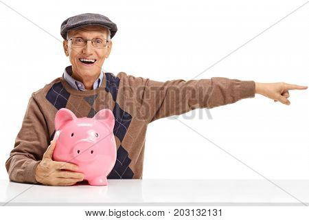 Senior with a piggybank sitting at a table and pointing right isolated on white background
