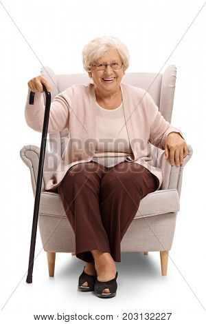 Elderly woman with a cane sitting in an armchair and looking at the camera isolated on white background