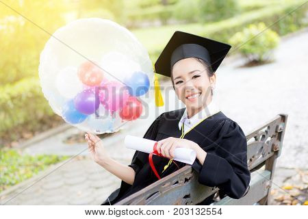 Portrait of happy young female graduates in academic dress and square academic cap holding word quotes of CONGRATS GRAD on balloon after convocation ceremony.