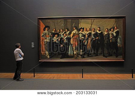 AMSTERDAM, THE NETHERLANDS - MAY 4, 2016: Visitors and The Meagre Company (1637) by Frans Hals at the famous Rijksmuseum in Amsterdam, Netherlands.