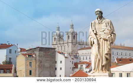 The statue of Saint Vincente with church of Sao Vincente de Fora on the Largo de Santa Luzia