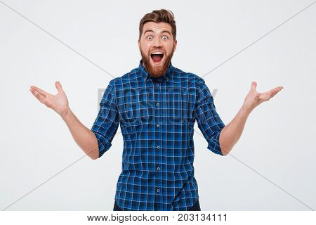 Surprised happy bearded man in casual clothes looking camera with opened mouth isolated over white