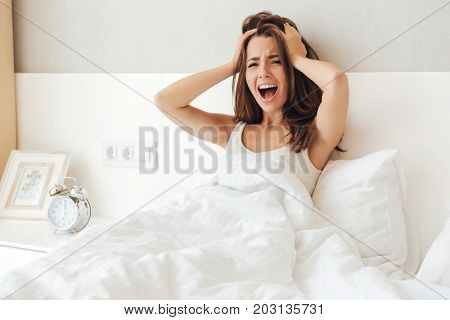 Angry young girl holding hands at her head and screaming while laying in bed in the morning