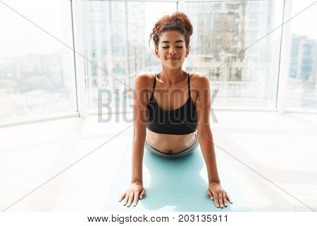 Young african smiling rested woman in sportswear making exercises at home