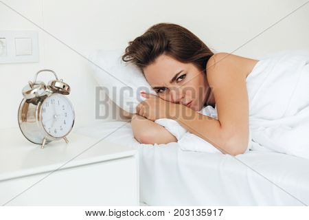 Angry pretty woman laying in bed in the morning and looking at camera