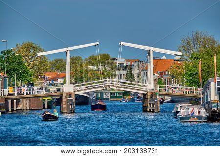 HAARLEM, NETHERLANDS - MAY 6, 2017: Boat passing under Gravestenenbrug bridge famous tourist landmark on Spaarne river in Haarlem, Netherlands