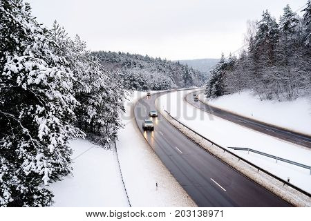 Beautiful View Of A Highway On Winter Day. Cars Driving Through Pine Forest Covered With Snow.
