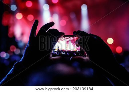Hand with a smartphone records live music festival, Taking photo of concert stage, live concert, music festivall, happy youth