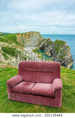 Red velvet sofa on the green mountain over blue sea and sky background