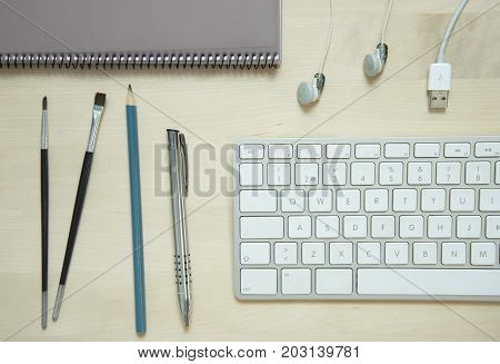 computer keyboard pen pencil notepad white earphone on wood table or desk business office lay flat