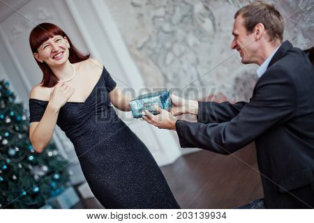 man gives a woman a gift for the New Year. A smiling man gives a Christmas present.