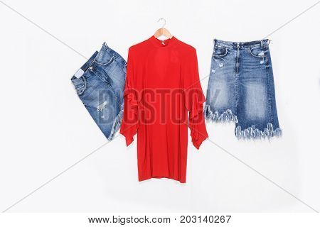 female red sundress with shirt, shorts jeans on hanging isolated