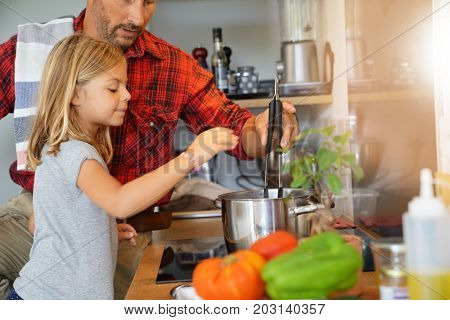 Daddy with daughter cooking together in home kitchen