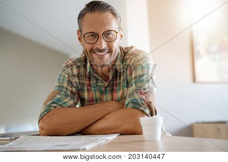 Handsome mature man at home reading newspaper