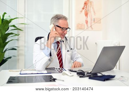 Doctor talking on the phone in his studio
