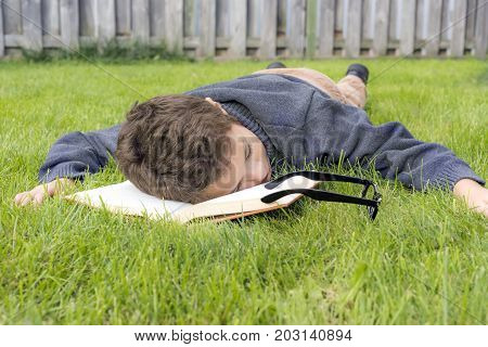 Boy Fallen Asleep Lying Down Reading Outdoors In The Grass, Head On Open Book, Glasses