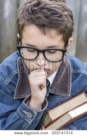 Preteen Boy With Black Glasses Holding Books And Leaning Face On Hand, Thinking, Perplexed Or Sad Ex