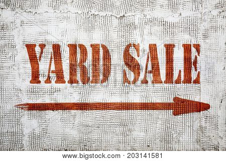 yard sale - graffiti sign with an arrow on stucco wall