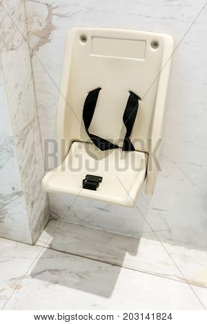 Folding Toddler Safety Chair Mounted On Wall In Public Restroom.
