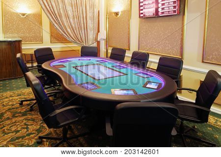 Empty hall in casino with electronic green poker table and soft armchairs