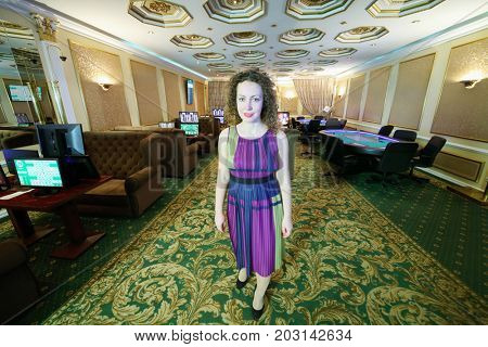 Pretty curly smiling woman stands on carpet in casino with electronic poker tables