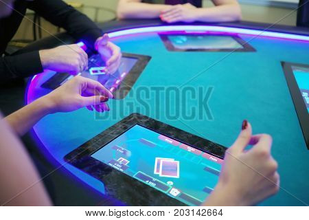 Hands of two women and man play poker in casino with electronic table, focus on woman hand
