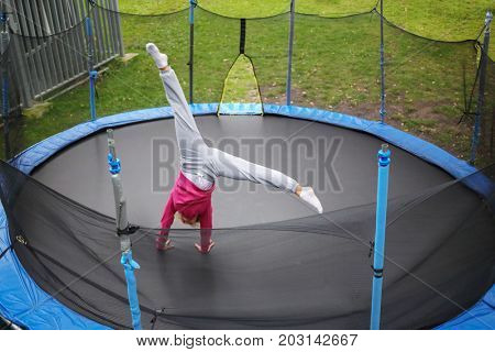 Slim woman tumbles on trampoline outdoor at summer day, top view