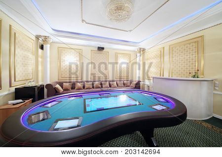 Private hall in casino with electronic poker table and soft couch