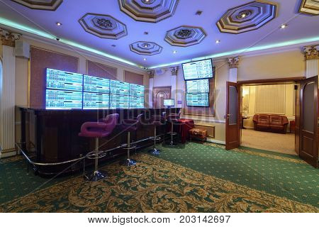 Empty wooden counter and lot of screens in luxury bookmaker office with carpet, my photo in frame