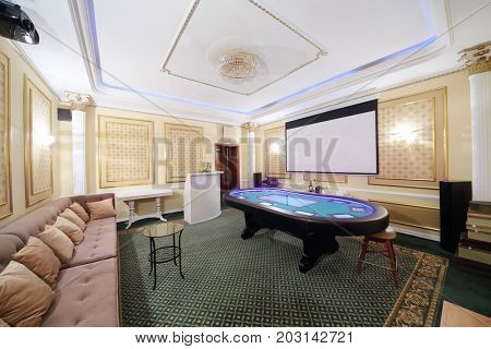 Private hall in casino with modern electronic poker table and screen on wall