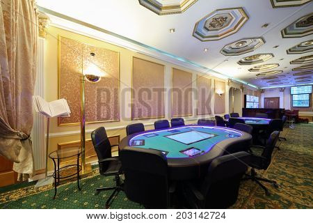 Casino with modern electronic poker table and screens on wall, my photo on screens