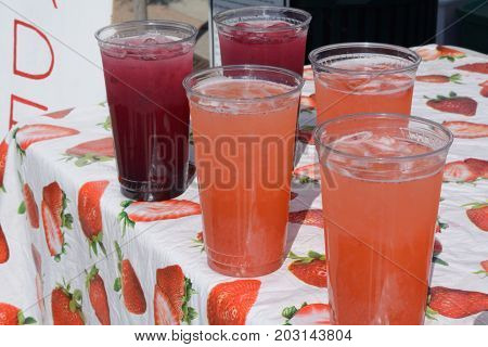 Glasses of blueberry and strawberry beverages with ice at lemonade stand at farmer's market