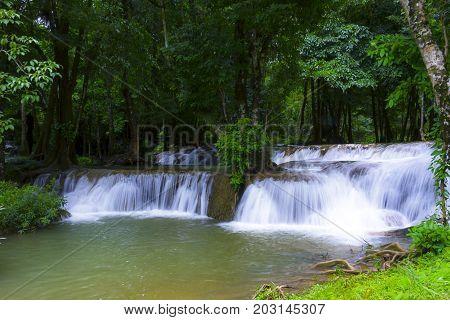 Waterfall in green forest and the rain in Kanchanaburi Thailand