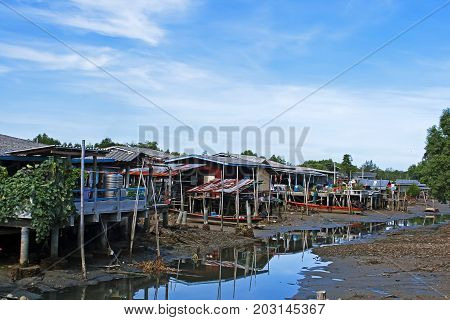 Community and old house with blue sky in countryside Thailand.
