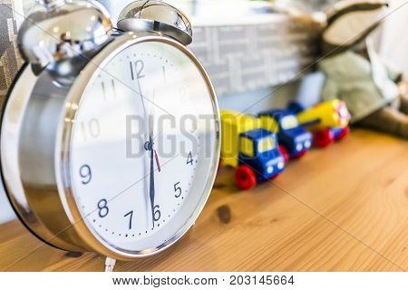 Closeup Of Modern Twin Bell Ring Analogy Clock On Wooden Table Desk Nightstand With Toy Trucks In Bo