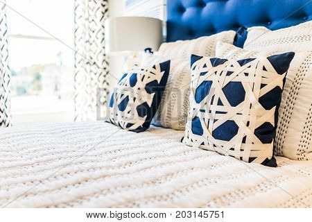 Closeup Of New Bed Comforter With Decorative Pillows In Bedroom In Staging Model Home, House Or Apar