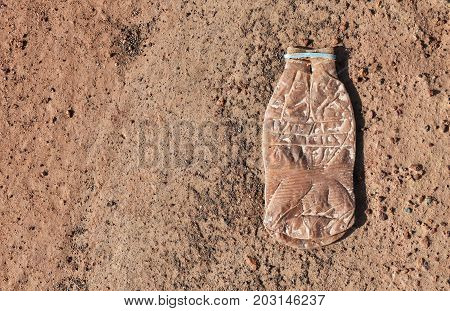 plastic bottle and little stone on dry soil ground