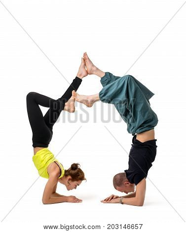 Two girls doing yoga handstand together isolated on white