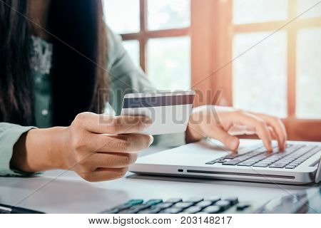 Hipster woman hands holding laptop and using credit card for online shopping.Online shopping concept.