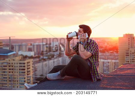 A hipster man drinks coffee and talks on his cell phone. He sits on the roof of a high-rise building at sunset. Portrait on a background of sunset and cityscape