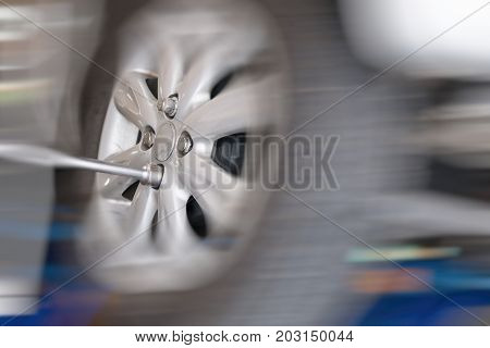 Mechanic Changing Car Wheel In Auto Repair Shop. Serviceman Wrenching Spanner To Replace Vehicle Tyr