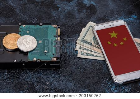 Bitcoin coin on HDD with smartphone with China flag