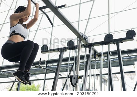Young Woman Execute Exercise With Machine In Fitness Center. Female Athlete Training In Gym. Sporty
