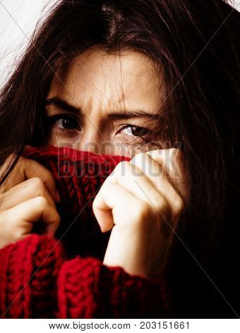 young brunette gloomy woman in sweater all over her face, messed hair close up