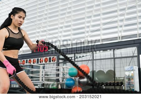 Young Woman Execute Exercise In Fitness Center. Female Athlete Training With Battle Rope In Gym. Spo