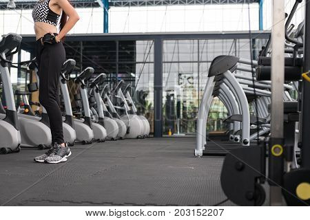 Young Woman Standing With Hands On Hip In Fitness Center. Female Athlete Prepare For Training In Gym