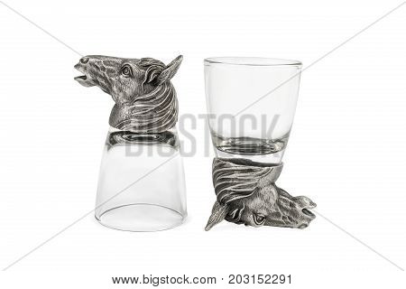 Two glasses for vodka with metal heads of a horse on the bottom, isolated on a white background
