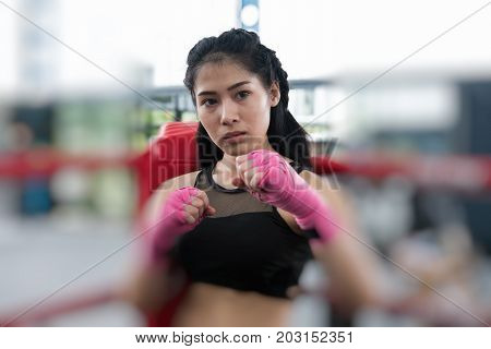Young Woman Posing In Combat Stance In Fitness Center. Female Boxer Standing In Boxing Ring In Gym.