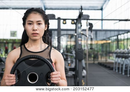 Young Woman Bodybuilder Execute Exercise In Fitness Center. Female Athlete Lift Heavy Weight Barbell